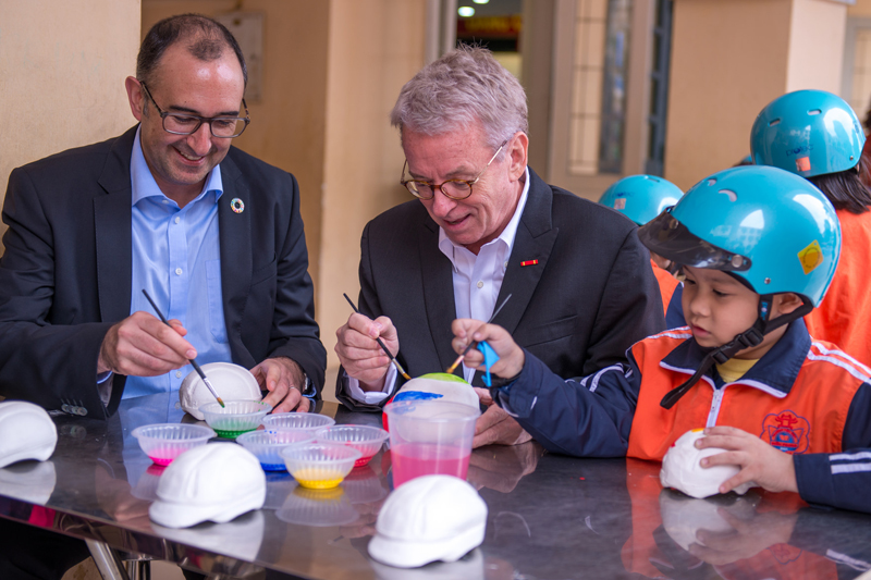 Saul Billingsley and Greig Craft joined schoolchildren at Tien Phong Primary School to paint commemorative model helmets.